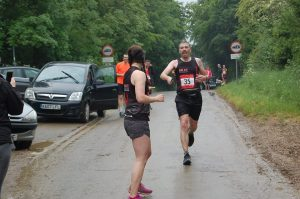 Photo of two BRAT runners handing over on the Hilly 100 course